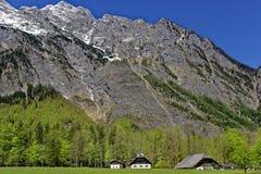 Lantgård i dalen på en bergmassiv Arkivbild