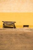 Lantlig bänk bredvid den målade väggen Arkivfoto