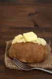 Lantlig bakad potatis med smör Fotografering för Bildbyråer