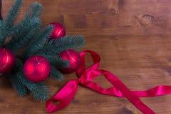 Lantlig bakgrund med bollar och band för jul för granfilial röda Royaltyfria Bilder