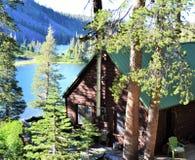 Lantlig bergkabin ovanför kolossala sjöar Fotografering för Bildbyråer