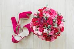 Lantlig bröllopbukett med vita och röda rosor, karmosinröda pioner och skor för sammetbrud` s på ett trägolv Närbild Royaltyfria Foton
