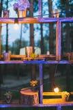 Lantlig bröllopdekor, hyllaställning med lila ordning och suc Arkivbilder