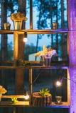 Lantlig bröllopdekor, hyllaställning med lila ordningar och su Arkivbilder
