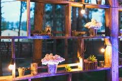 Lantlig bröllopdekor, hyllaställning med lila ordningar och su Royaltyfria Bilder