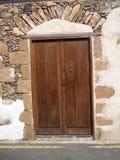 Lantlig brun dörr i Fuerteventura med stenar Arkivbilder