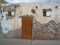 Lantlig brun dörr på en fördärva i Fuerteventura med bruna stenar Arkivfoto