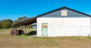 Lantlig byggnad med den färgrika rostiga dörren i ett gräs- fält, med överhäng och rostiga vätskebehållare arkivfoto