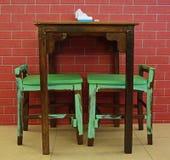 Lantlig design av tabellen och stolar mot tegelstenbakgrund Arkivfoton