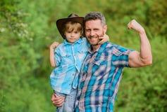 Lantlig familj V?xande gullig cowboy Liten hj?lpreda i tr?dg?rd Pys och fader i naturbakgrund Ande av arkivbild