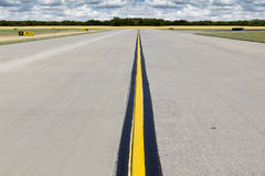 Lantlig flygplatslandningsbana med den ljusa gula linjen och den guld- wheatfielden Arkivbild