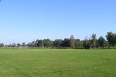 Lantlig fotboll, fotbollgrad som tas från åskådarläktaren på en solig vår, sommardag Arkivbild