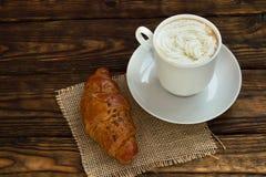 Lantlig franska Kopp av varmt kaffe och en giffel på en trätabell Royaltyfria Bilder