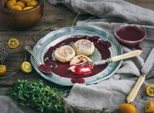 Lantlig frukostuppsättning Rysk ost bakar ihop på en tappningmetallplatta med lingondriftstopp, nya kumquats, timjan, garneringre Royaltyfri Foto