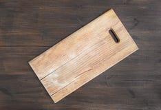 Lantlig fyrkantig träskärbräda på ett mörkt träskrivbord Royaltyfri Bild