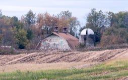 Lantlig gammal ladugård med en rund silo och härliga gavlar royaltyfria bilder