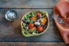 Lantlig grönsakbunke med salt och gaffeln royaltyfri foto