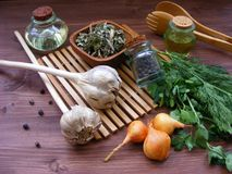 Lantlig grönska: ny persilja och dill, löken, vitlök, olivolja i exponeringsglas, torkar kryddor i bunke och enbär Arkivfoto