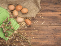 Lantlig idérik bakgrund med bruna ägg, säckväv, sugrör, dokument med olika förslag och torkar blommor på trätabellen från gamla p Royaltyfri Foto