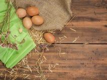 Lantlig idérik bakgrund med bruna ägg, säckväv, sugrör, dokument med olika förslag och torkar blommor på trätabellen från gamla p Arkivbild
