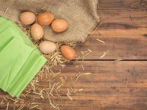 Lantlig idérik bakgrund med bruna ägg, säckväv, sugrör och dokument med olika förslag på trätabellen från gamla plankor Arkivfoton