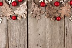Lantlig julöverkantgräns med träprydnader och röda struntsaker på åldrigt trä Royaltyfria Bilder