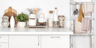 Lantlig kökbänk och stege med olika redskap på vit fotografering för bildbyråer