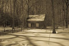 Lantlig kabin i snöig trän i Michigan i sepia Arkivfoton