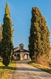 Lantlig kyrka för litet 13th århundrade med cypressar Royaltyfri Bild