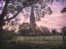Lantlig kyrka på soluppgång Fotografering för Bildbyråer