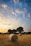 Lantlig landskapbild av sommarsolnedgången över fält av höbaler Royaltyfria Foton