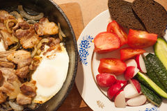 Lantlig mat för rik lantlig frukost, stekt ägggriskött och nya grönsaker på en platta Fotografering för Bildbyråer