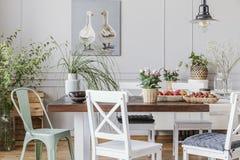 Lantlig matsal med den långa tabellen och vita stolar och oljamålning på den gråa väggen, verkligt foto royaltyfri fotografi
