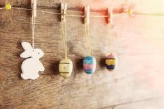 Lantlig påskbakgrund: Tappning målade ägg och den vita kaninen hänger på klädnypor mot den gamla bruna träväggen Den lyckliga man royaltyfri foto