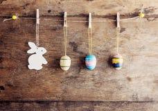 Lantlig påskbakgrund: Tappning målade ägg och den vita kaninen hänger på klädnypor mot den gamla bruna träväggen Den lyckliga man royaltyfria bilder