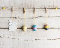 Lantlig påskbakgrund: Tappning målade ägg och den vita kaninen hänger på klädnypor mot den gamla vita träväggen Den lyckliga mann royaltyfri bild