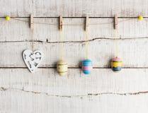 Lantlig påskbakgrund: Tappning målade ägg och vit hjärta hänger på klädnypor mot den gamla vita träväggen royaltyfria bilder