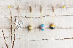 Lantlig påskbakgrund: Tappning målade ägg och vit hjärta hänger på klädnypor mot den gamla vita träväggen Den lyckliga mannen tyc royaltyfria foton