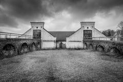 Lantlig plats för tappning, dramatisk främre sikt av det svartvita gamla lantliga slitna för ladugårdbyggnad för sten två lantbru fotografering för bildbyråer