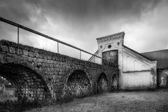 Lantlig plats för tappning, dramatisk främre sikt av svartvit gammal lantlig sliten byggnad för stenladugårdlantbrukarhem med mör arkivfoto