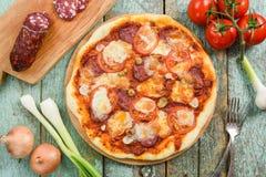 Lantlig rund pizza med salami Körsbärsröda tomater, salami, vitlök, Royaltyfri Fotografi