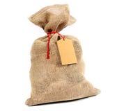 Lantlig säckvävsäck med en gåvaetikett Arkivfoto