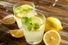 Lantlig sammansättning med nytt sammanpressad hemlagad kall lemonad i flaska och exponeringsglas med kondensationssmå droppar fotografering för bildbyråer