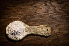 Lantlig sked för stiliserad gammal lera Keramisk sked med mjöl på en wo Arkivfoton