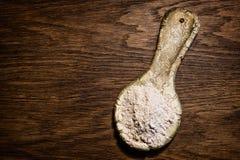 Lantlig sked för stiliserad gammal lera Keramisk sked med mjöl på en wo Royaltyfri Fotografi