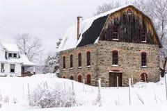 Lantlig sten- & träladugård i snö - vintereftermiddag - New York Arkivbild