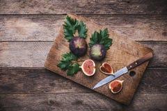 Lantlig stil klippte fikonträd med kniven på skärbräda och träta Royaltyfria Bilder