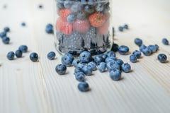 Lantlig sund frukost med blåbäret och jordgubben i en glass krus på en trätabell Exponeringsglas av mogna bär Royaltyfria Bilder