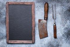 Lantlig svart tavla med den köttköttyxan och gaffeln royaltyfri fotografi
