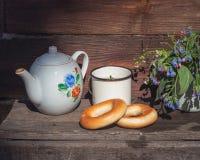 Lantlig tebjudning i den öppna luften, te med baglar En liten bukett av vildblommor arkivfoton